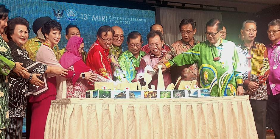 Abang Johari (in red batik), officials and guests in a cake-cutting ceremony marking Miri City Day celebration.