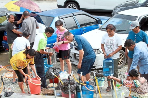 (Far right) Taman Andalas residents filling containers with water from public taps set up in front of Masjid Jamek Ar Rahimiah in Klang. — Filepic