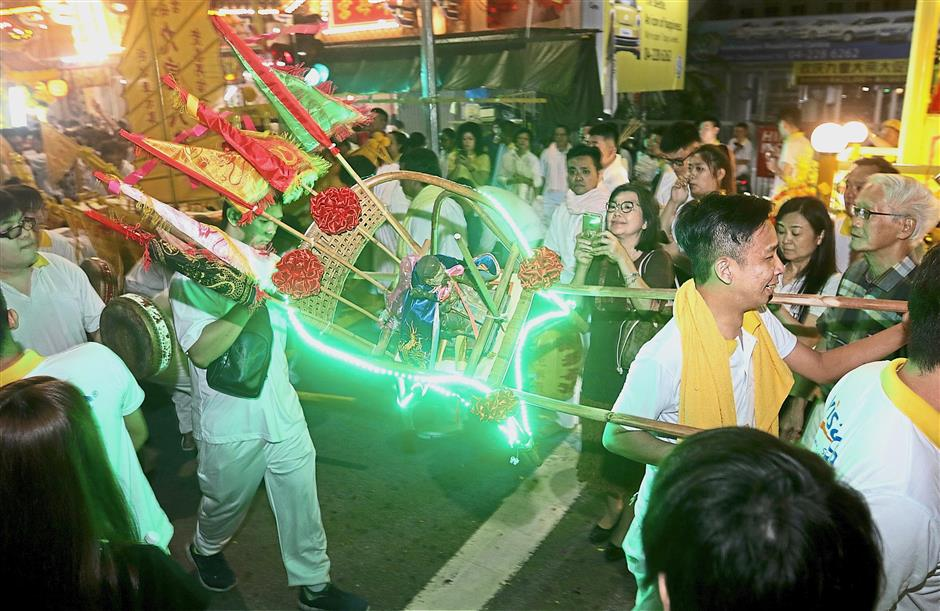 Devotees carrying a sedan chair on two poles during the parade.