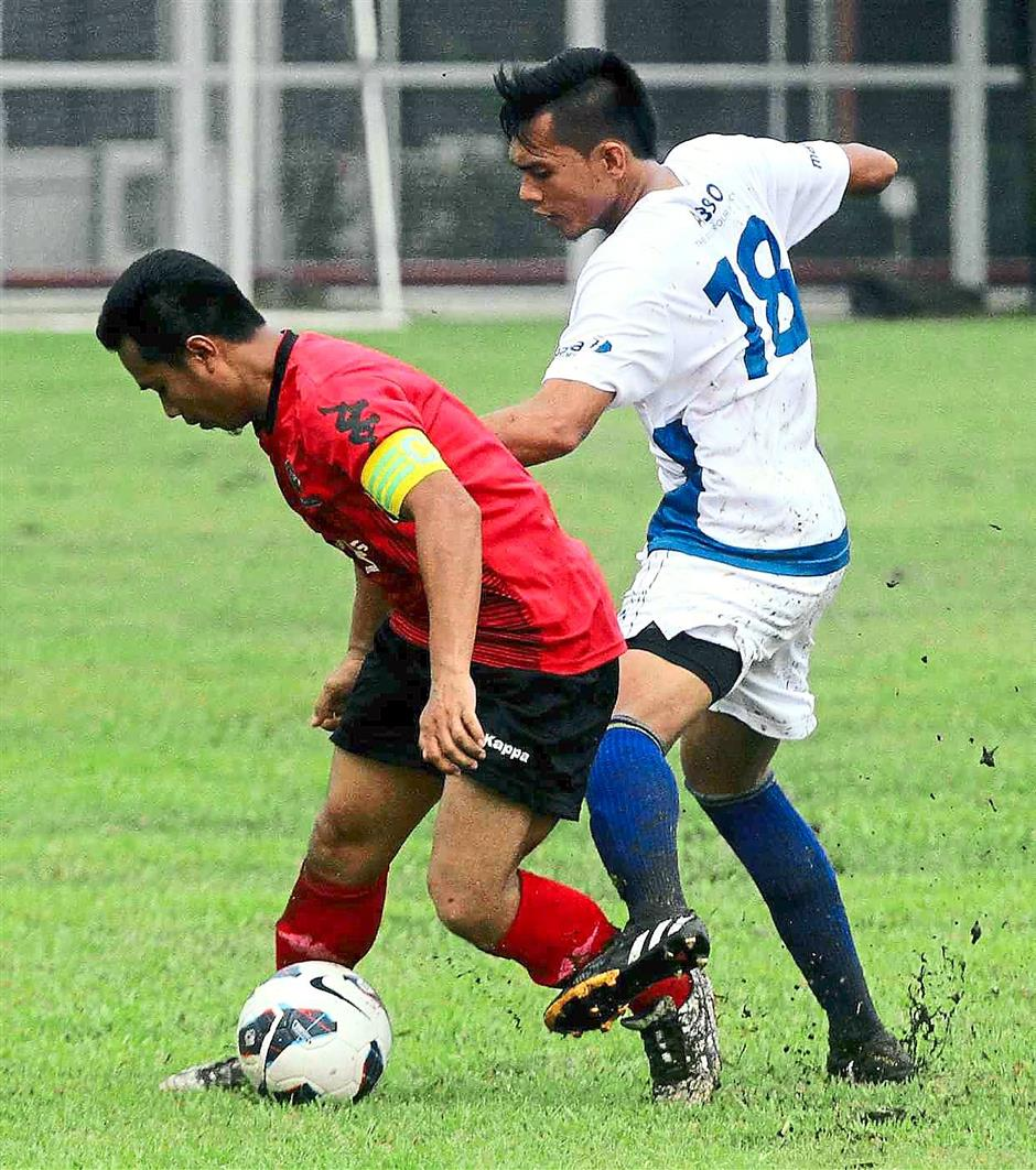 No way out: Proton captain Mohd Amirul Hisham Ismail (left) involved in a tussle for the ball with Akmal Hakim.