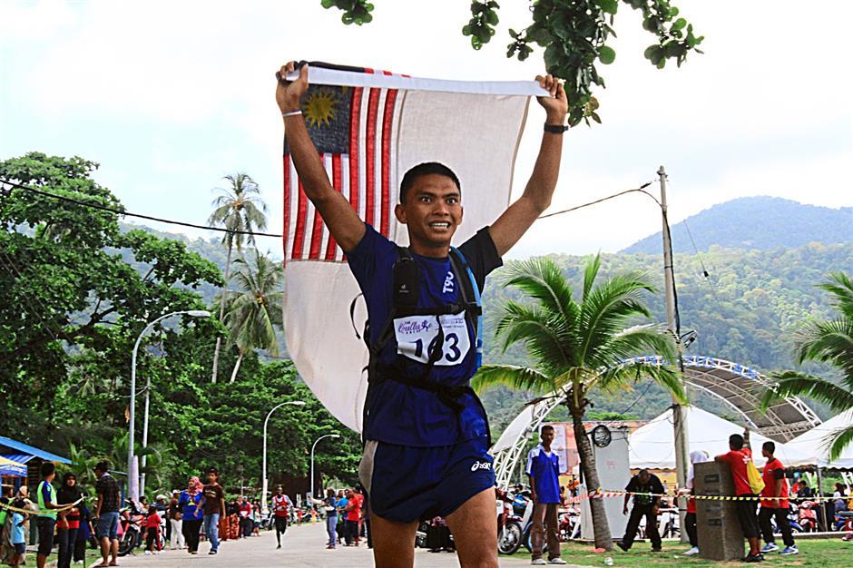 L/Kpl Raziz Malangkis waving the Malaysian flag upon reaching the finishing line at the Sultan Ahmad Shah Tioman International Eco Challenge 2014.