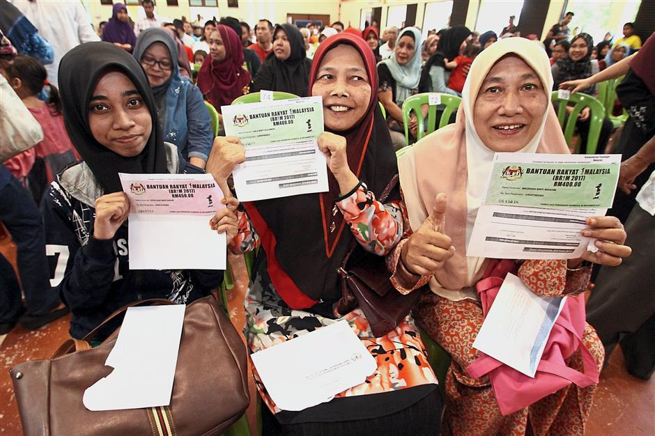 A file image of a group of BR1M recipients after receiving their vouchers in Bidor on March 3. Another area covered in the manifesto is the raising of the BR1M payment by RM150 for single people with household incomes of RM3,000 and below.