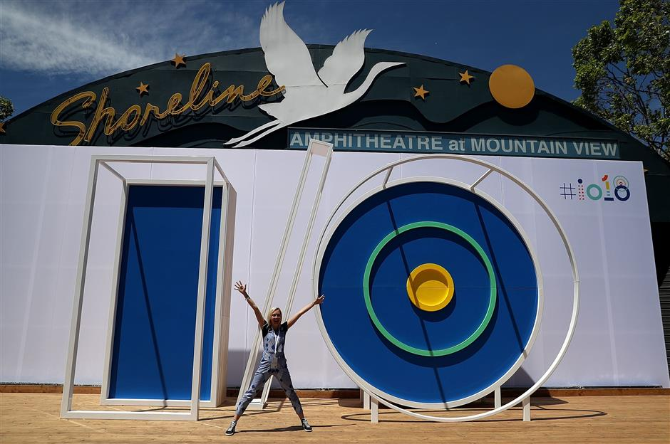MOUNTAIN VIEW, CA - MAY 08: An attendee poses for a photo in front of the Google I/O logo at the Google I/O 2018 Conference at Shoreline Amphitheater on May 8, 2018 in Mountain View, California. Google\'s two day developer conference runs through Wednesday May 9.   Justin Sullivan/Getty Images/AFP == FOR NEWSPAPERS, INTERNET, TELCOS & TELEVISION USE ONLY ==