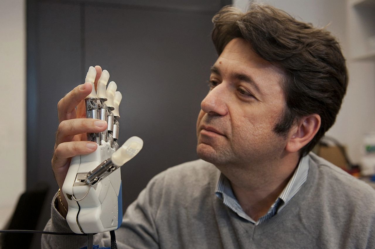 HUGE DEAL: An undated handout photo showing neuroengineer Silvestro Micera holding a bionic hand. To feel what you touch — that's the holy grail for artificial limbs. In a step toward that goal, European researchers created a robotic hand that let an amputee feel differences between a bottle, a baseball and a mandarin orange. — Science Translational Medicine