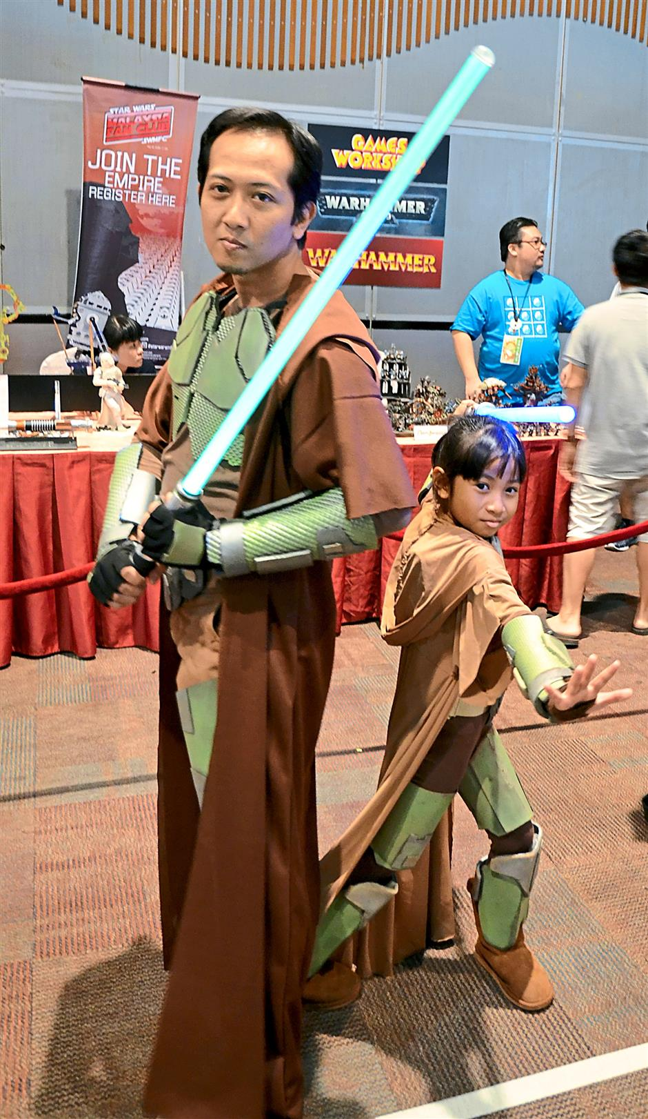 Sami Sukit, 35 (left) and his daughter Dahlia Alyssa, 9 (right) posing for the camera in a curious mix of armour and brown Jedi robes, during the recent AniManGaki 2014 two-day gathering at Sunway Pyramid Convention Centre.