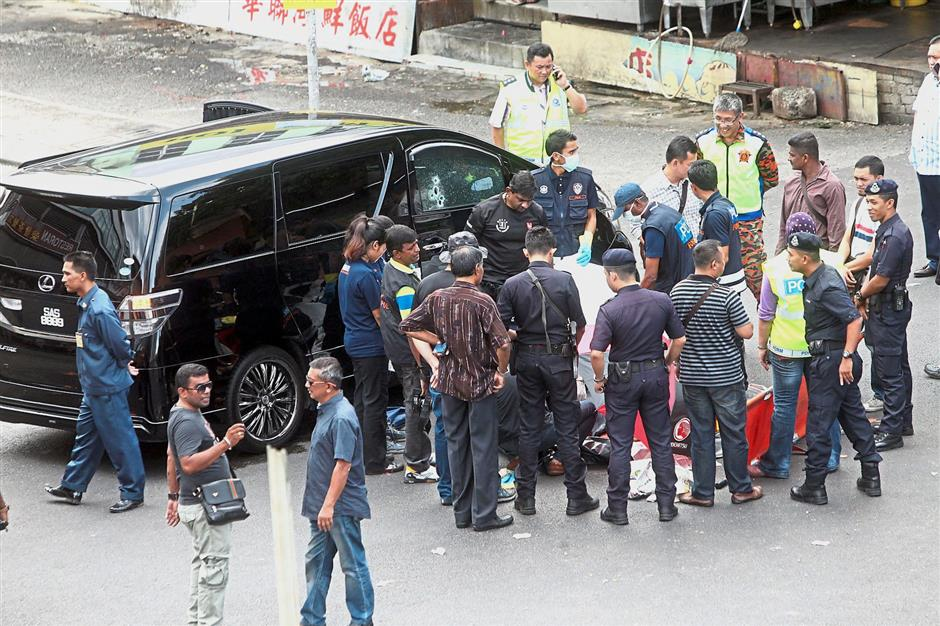 Gruesome episode: A filepic of police and forensic officers at the scene where Wong was gunned down by two unknown assailants at Taman OUG in July last year.