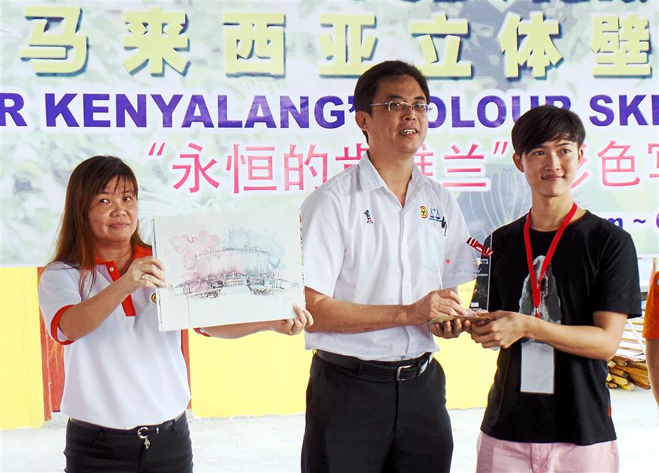 Congrats: Winner of the colour sketching contest Goh Chen Yang receiving his prize.
