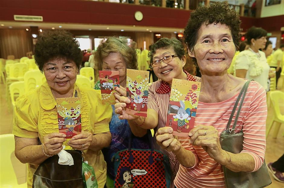 Senior citizens happily showing the red packets they received from Che Hoon Khor.