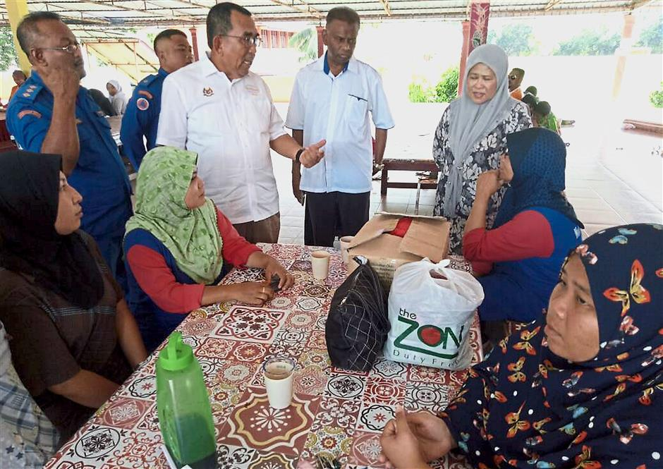 Xxxxx: ?Johari ?(standing-third left) ?with his wife Datin Seri Marziah Mohd Hashim (standing-right) and Kubang Pasu District Disaster Management secretariat's secretary Kapten (Civil Defence) Kamalruzamal Kasa (standing-left) conversing with a few female flood victims at a ?flood relief centre?.