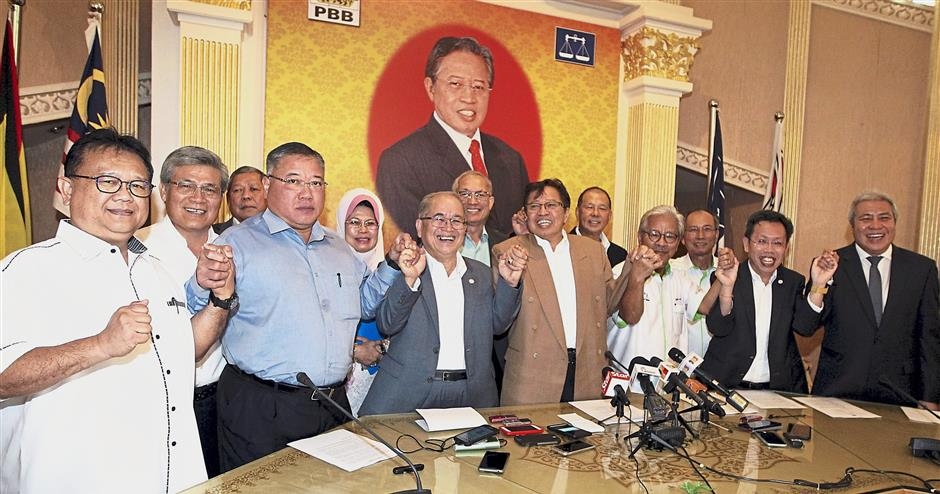 Group effort: Abang Johari (light brown jacket) and party leaders of PBB, PRS, PDP and SUPP joining hands in a show of unity after a meeting at the PBB headquarters in Kuching.