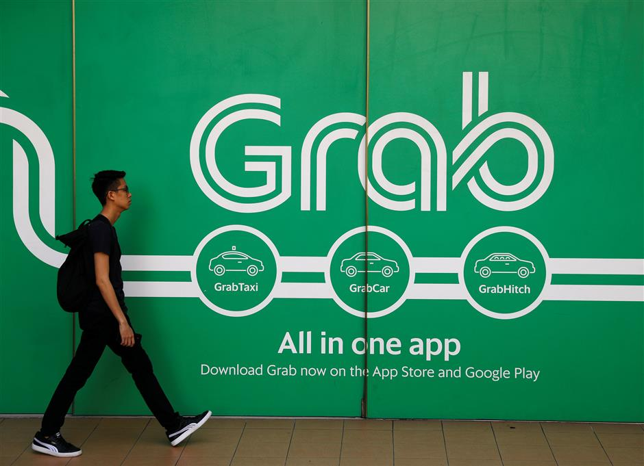A man walks past a Grab office in Singapore March 26, 2018. REUTERS/Edgar Su