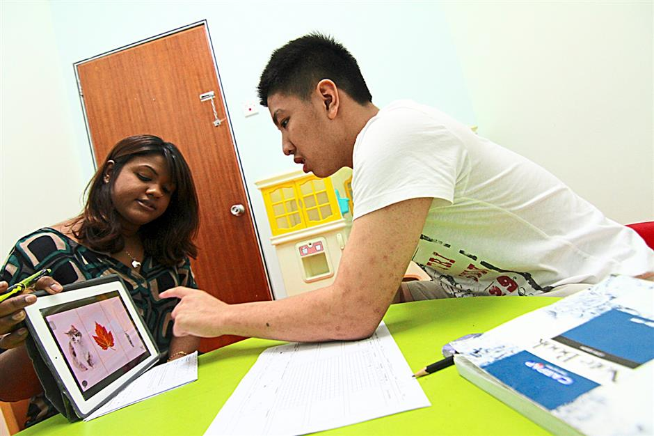 Visual learning: 15-year-old Yuan Li learns new words on his tablet with his teacher Dharshinie Vimalanathan.