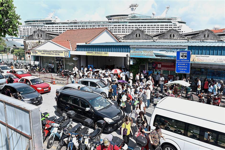 A filepix showing about 4,500 cruise passengers pouring out of Swettenham Pier from the 15-deck Voyager of the Seas towering in the background.