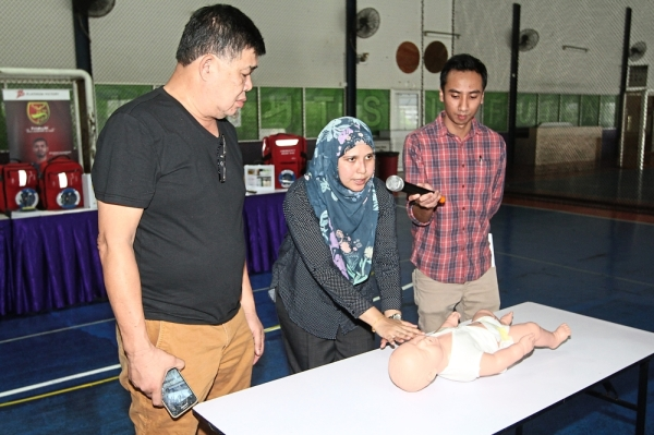 Dr Sherin showing Kuan (left) and a participant how to carry out CPR specifically for infants.