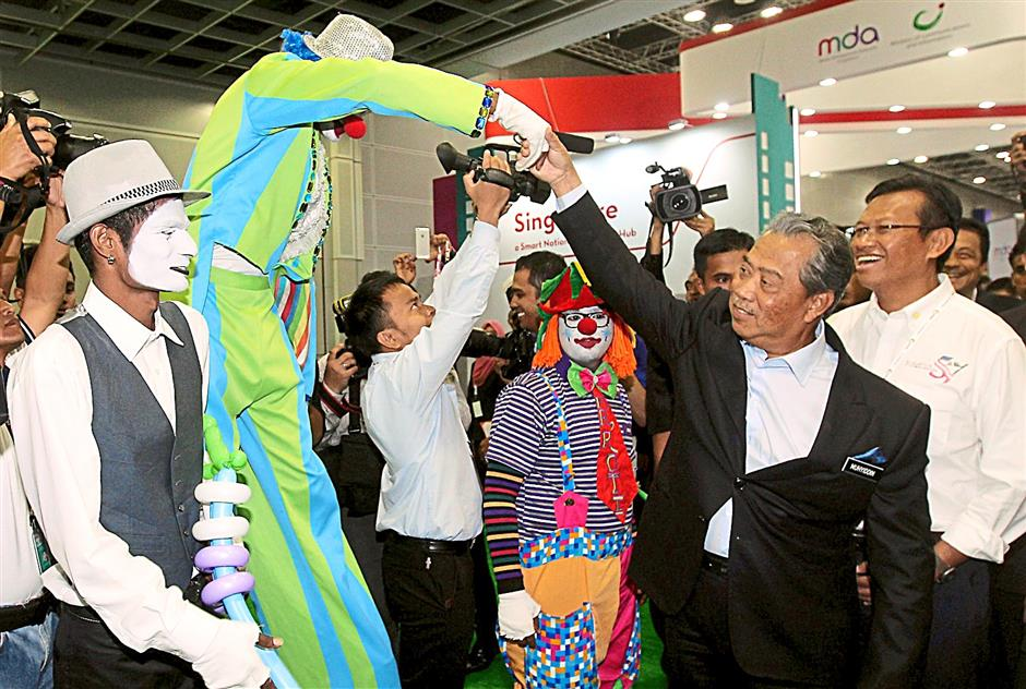 Nice to meet you, DPM:  Muhyiddin shaking hands with a clown as he tours the KL Converge! 2014 at the Kuala Lumpur Convention Centre. Looking on is Communication and Multimedia Minister Datuk Seri Ahmad Shabery Cheek (right).