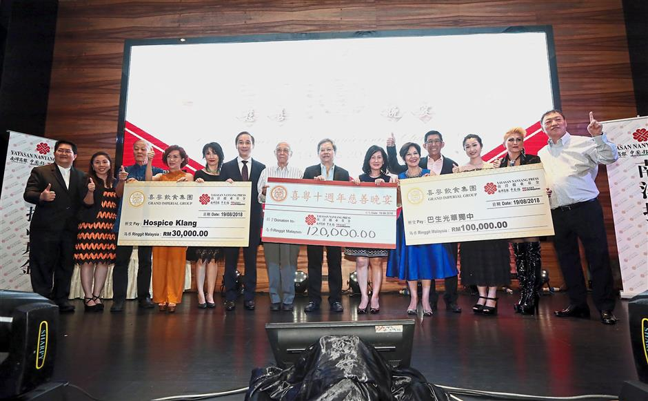 A mock cheque presentation by the Grand Imperial Group directors and senior management to the three beneficiaries –Yayasan Nanyang Press, Kwang Hua Private High School and Hospice Klang – at the charity night. — Photos: IZZRAFIQ ALIAS/The Star