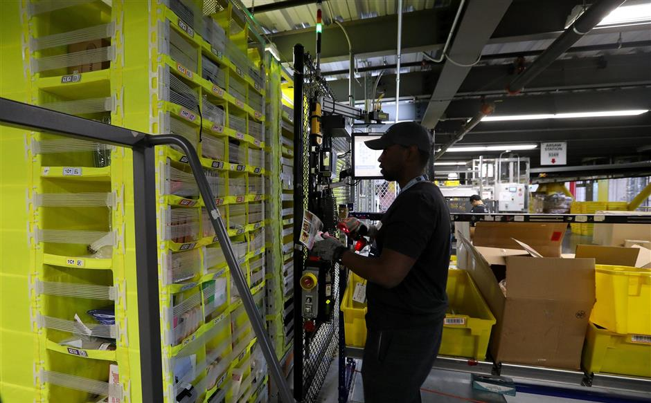 A worker scans items with a handheld device, then puts them in storage pods maneuvered by robots.  (Alan Berner/Seattle Times/TNS)