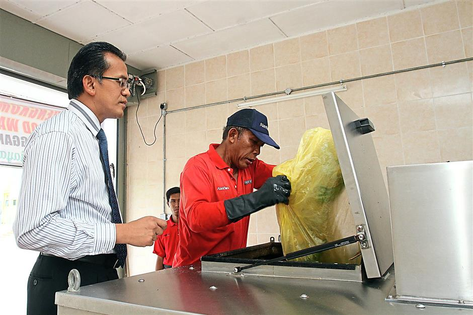 (left)Alam Flora chief executive officer Mohd Zain Hassan oversees his staff putting in the waste into the Bio-mate.