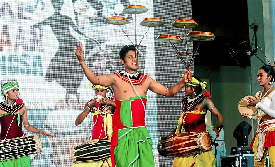 Amazing stunt: A member of the Sri Lankan Arpeggio Music and Dance group wowing the audience by balancing plates using his mouth and hand while being accompanied by traditional drummers.
