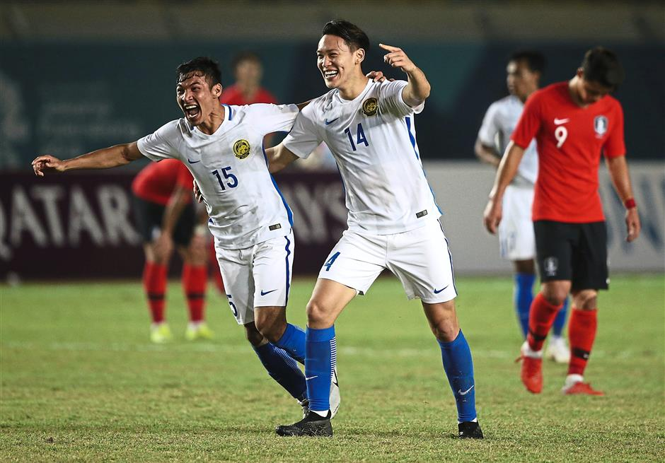 Malaysias Mohd Rizal Mohd Ghazali and teammate Dominic Tan, right, celebrate after they defeated South Korea 2-1 at the 18th Asian Games at Si Jalak Harupat Stadium in Bandung, Indonesia, Friday, Aug. 17, 2018. (AP Photo/ Achmad Ibrahim )