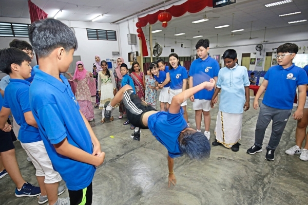 Children watching in awe as a pupil from Yeongdu Elementary School in South Korea perform a pop dance move during the cultural exchange at SJK (C) Chung Shan, Penang. — Photos: CHAN BOON KAI/The Star