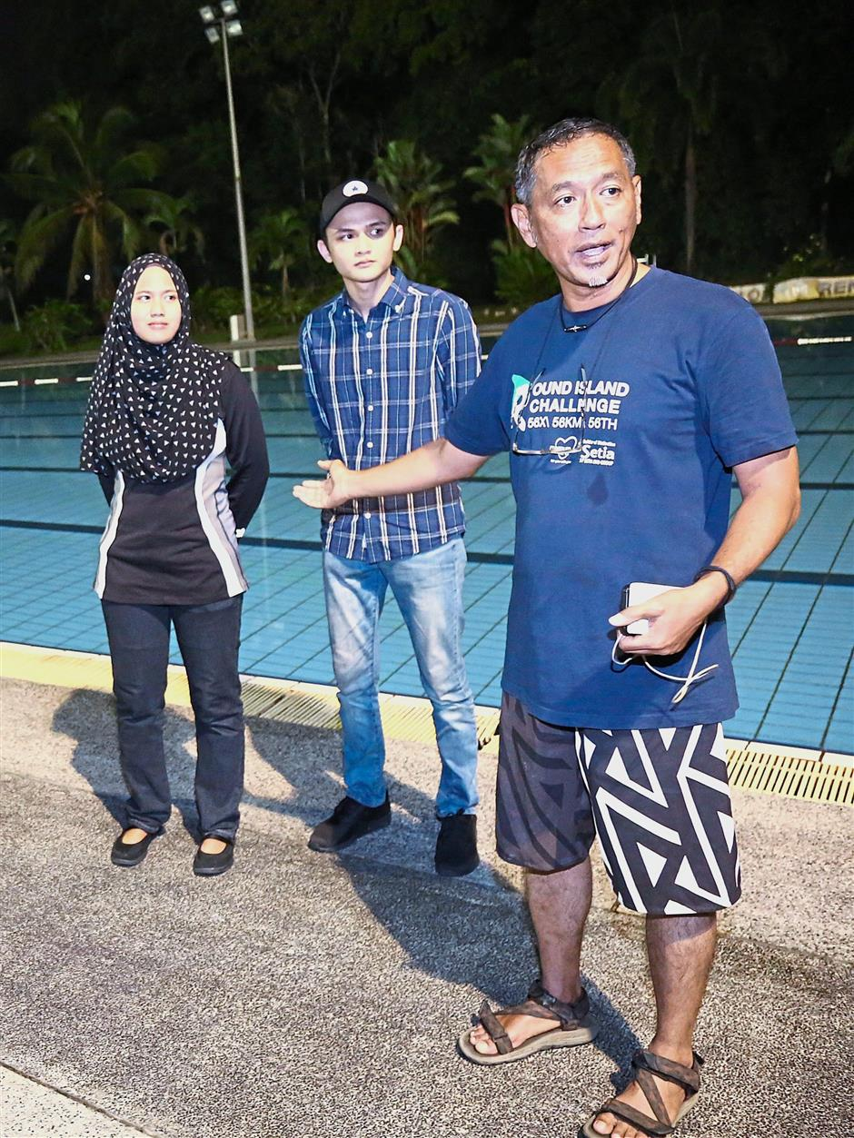 Abdul Razak (right) introducing siblings Zahra and Salman who were the last to swim across the Straits of Malacca.