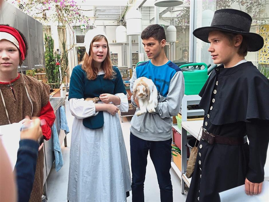 Pupils from Vesala Comprehensive School take care of the animals in the large greenhouse under the supervision of teachers.