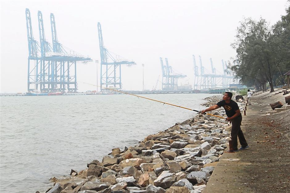 Fish can't wait: A man ignoring the haze in Port Klang as he tries his luck at fishing around 2.30pm yesterday.