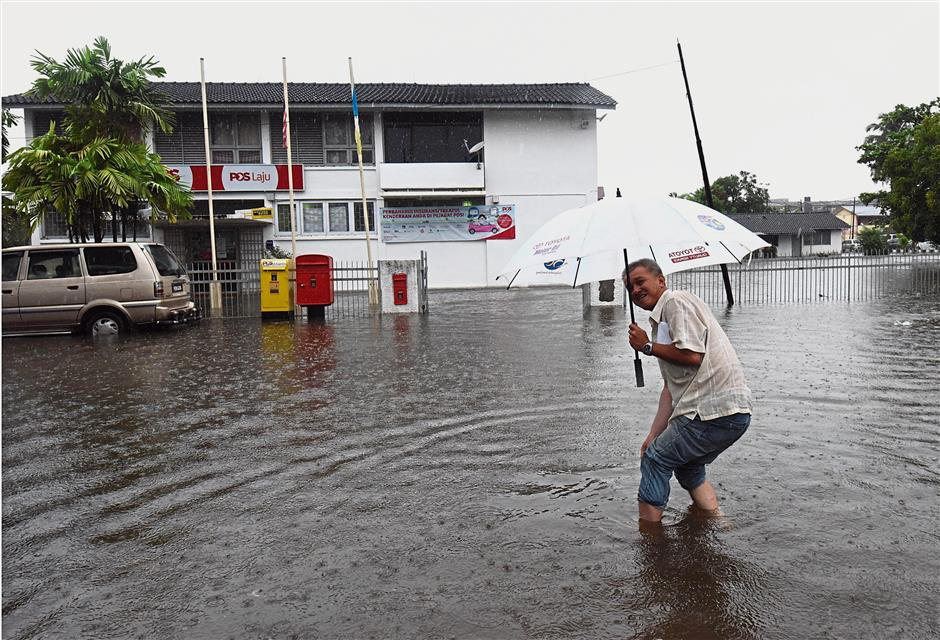 A customer rolling up his pants to get to the post office in Jalan Mak Mandin, Butterworth. (Right) State Welfare Department representatives registering flood victims at a relief centre in Mak Mandin.