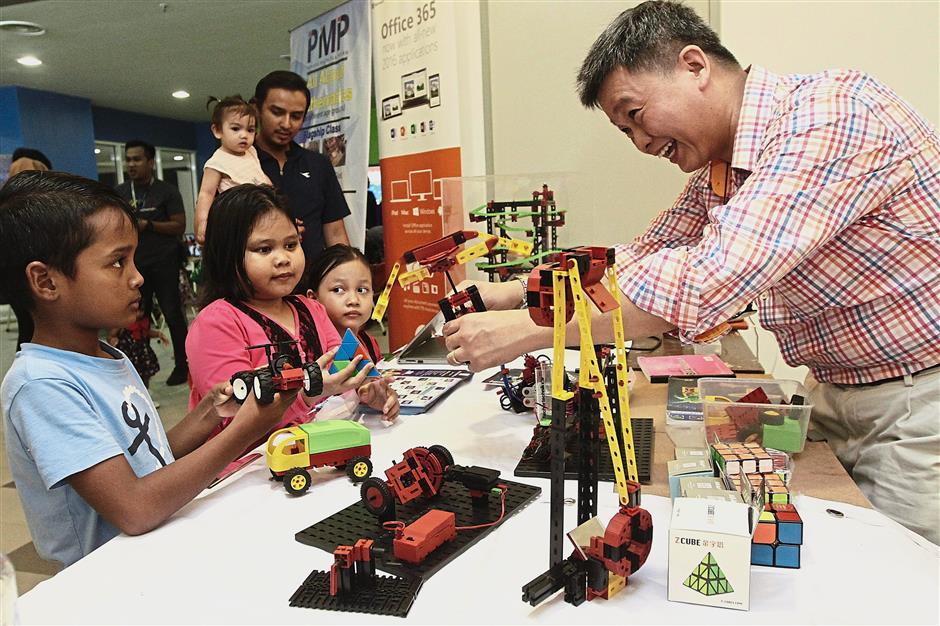 (Left) Children looking at the demonstration of some toy exhibits at the Batu Maung STEAM learning centre.