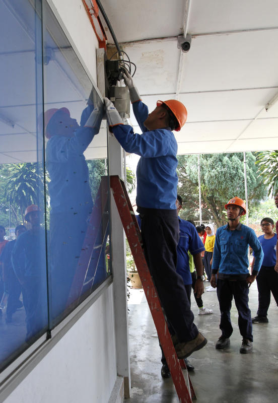 TNB employees reinserting the fuse to restore power in SK Methodist Petaling Jaya.