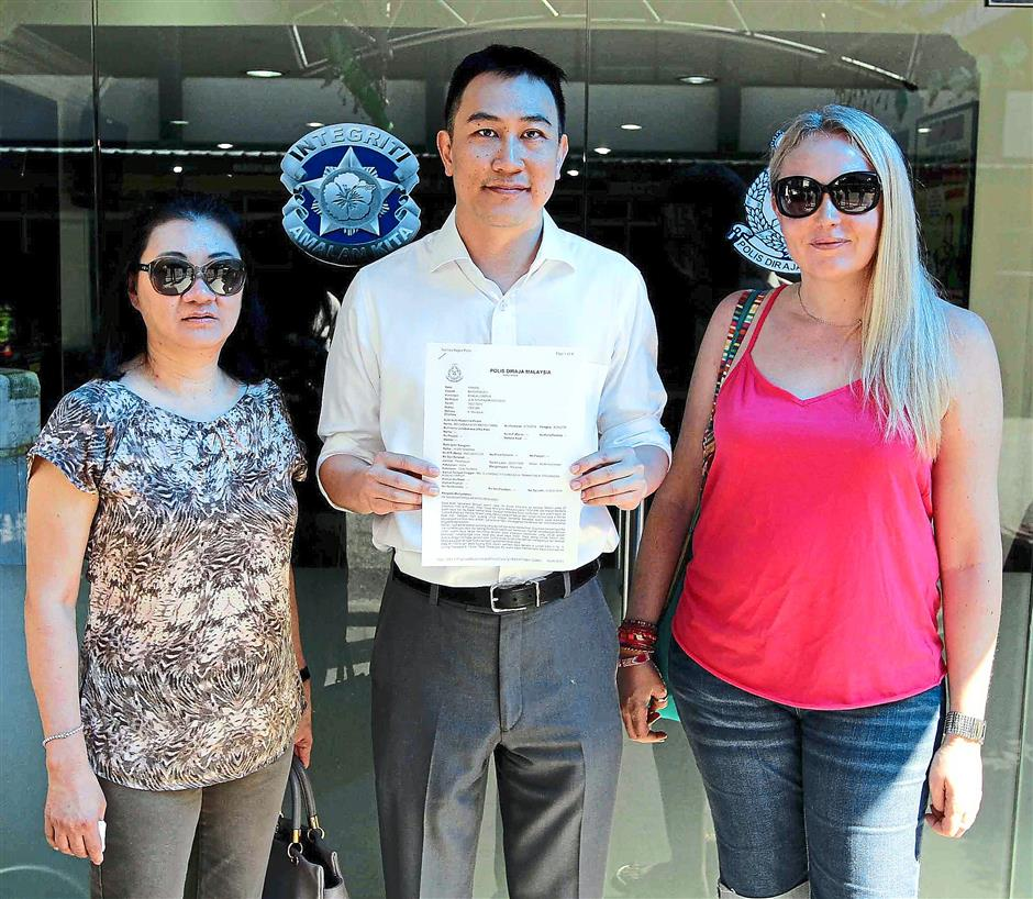 Relieved: (from left) Zehn Bukit Pantai residents Cynthia Tye, Ng and Alton, showing the police report lodged by them.