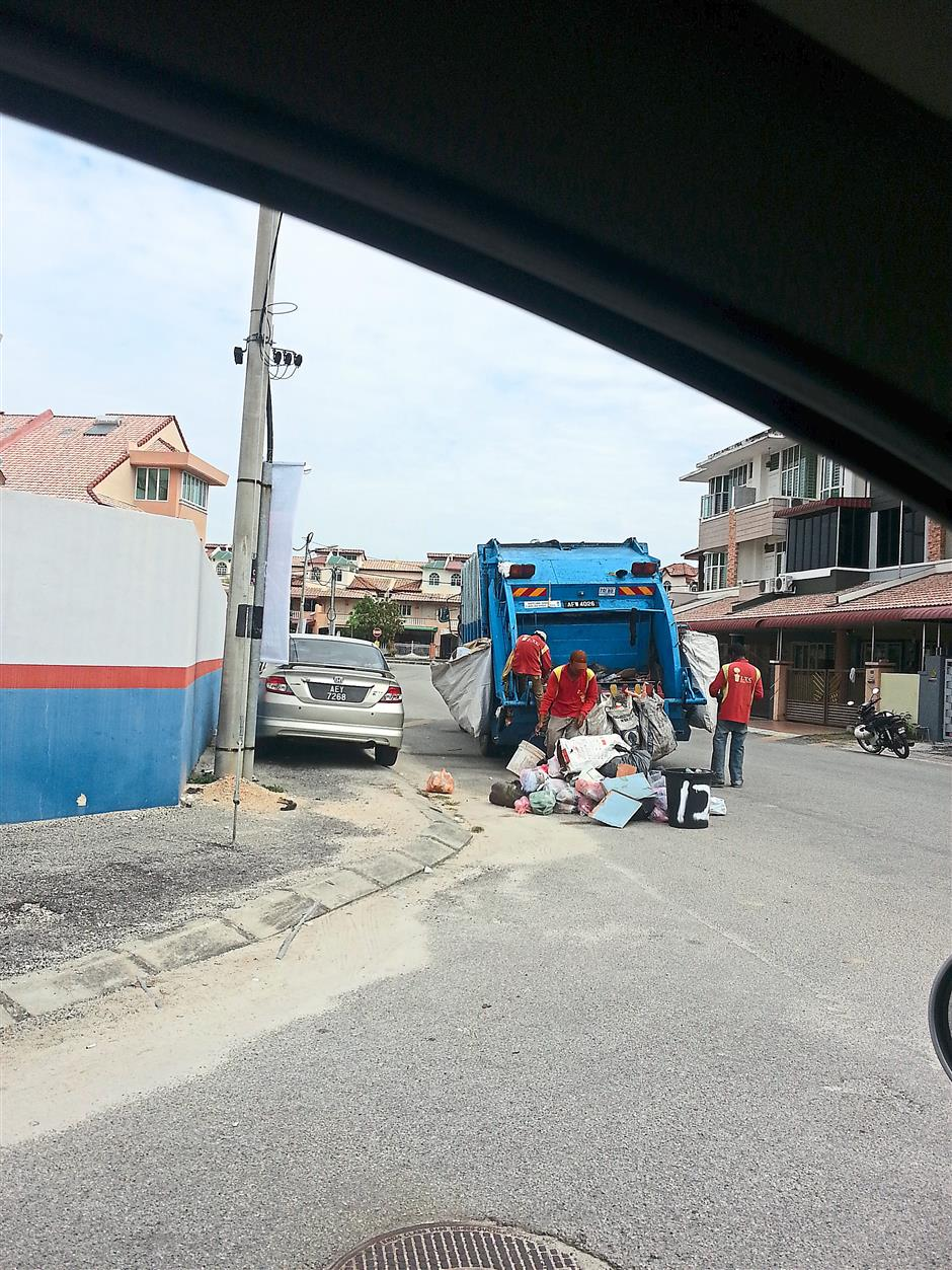 Sifting through: Garbage collectors going through the aforementioned rubbish heap to look for items they want.
