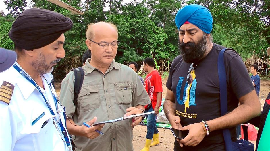 (From left) Private helicopter pilot Bagawan Singh, Centre for Orang Asli Concerns coordinator Colin Nicholas, and United Sikhs representative Rishiwant Singh at their base camp in Kuala Betis, Kelantan, planning aid drops to the orang asli in Pos Ber during the floods in January. The orang asli should be part of the planning and implementation of the 11th Malaysia Plan, Nicholas urges.