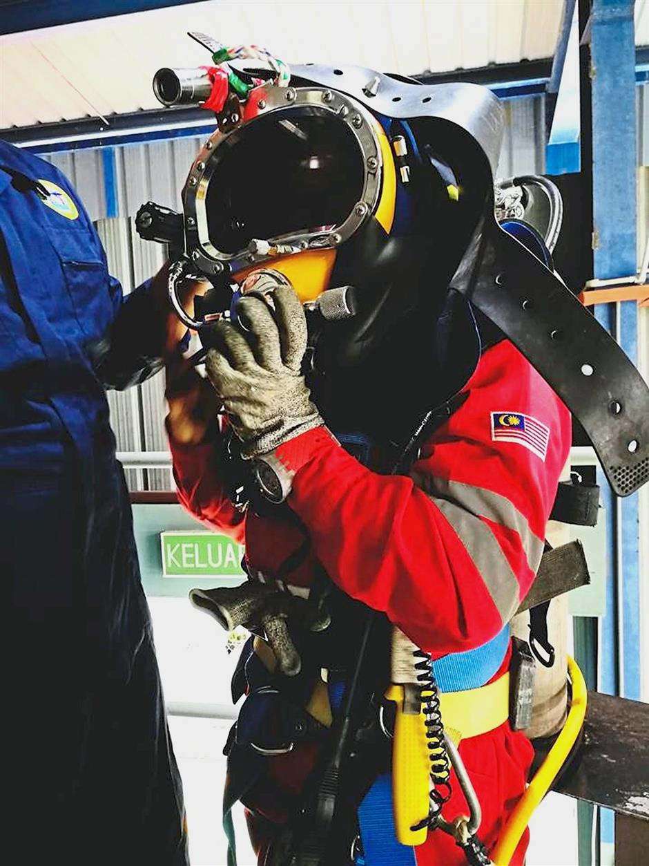 Nur Izzati Athirah dressed in full gear as she prepares to carry out her job under water.