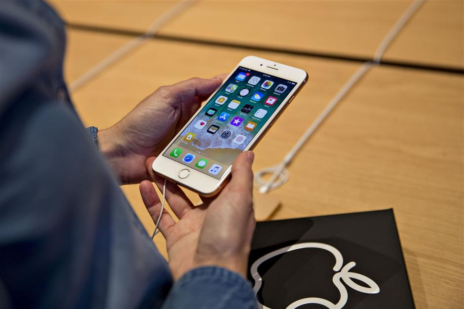 A woman looks at an iPhone 8 Plus on display during the opening of the new Apple Inc. Michigan Avenue store in Chicago, Illinois, U.S., on Friday, Oct. 20, 2017. The building features exterior walls made entirely of glass with four interior columns supporting a 111-by-98 foot carbon-fiber roof, designed to minimize the boundary between the city and the Chicago River. Photographer: Daniel Acker/Bloomberg