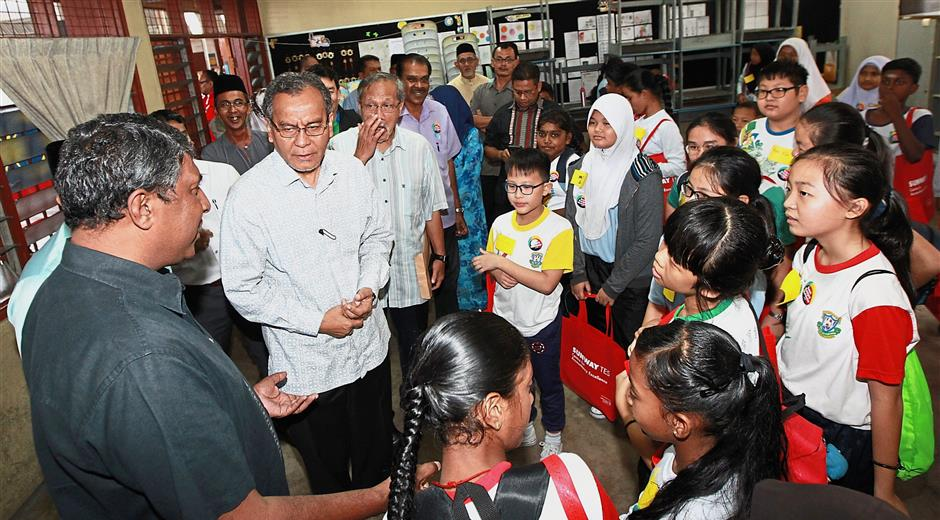 Nadarajah (left) tells Health Minister Dr Dzulkefly Ahmad (second from left) and Dr Idris (third from left) about the English camp.