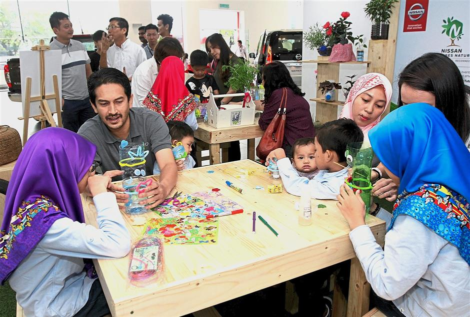During the herb-planting activity, customers planted herbs in plastic bottles while their children decorated the bottles with stickers and markers. —Photos: SAM THAM/The Star
