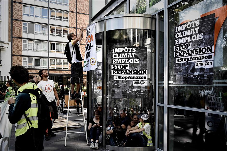 People glue placards on the frontage of the Amazon France offices during a blockade  organized by the NGO Amis de la Terre, in Clichy, on the outskirts of Paris, on July 2, 2019. (Photo by PHILIPPE LOPEZ / AFP)