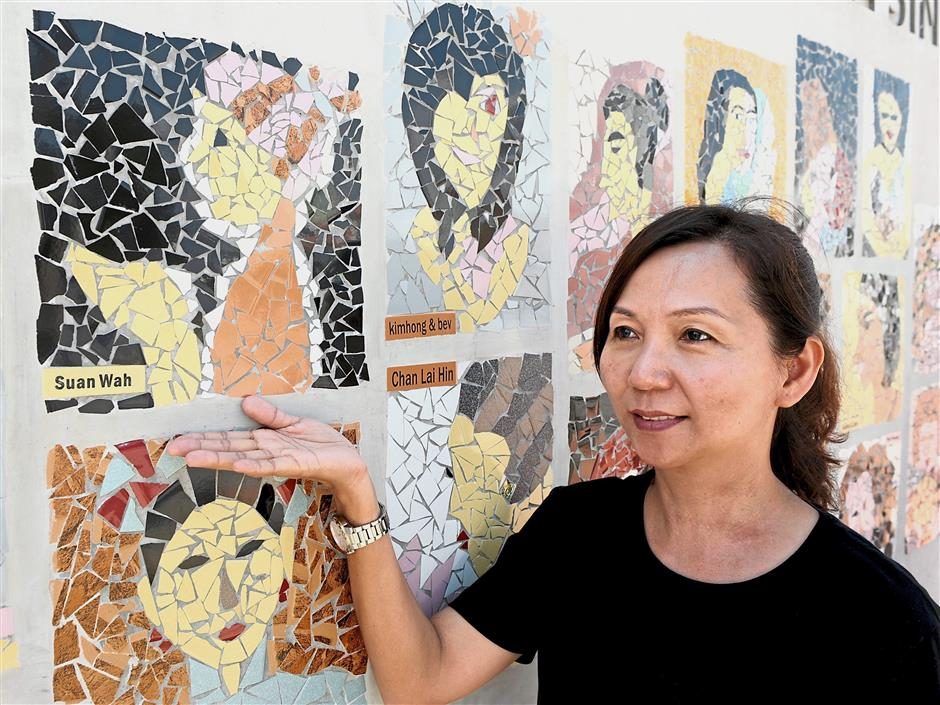 ^ Ang showing her mosaic artwork on the wall.