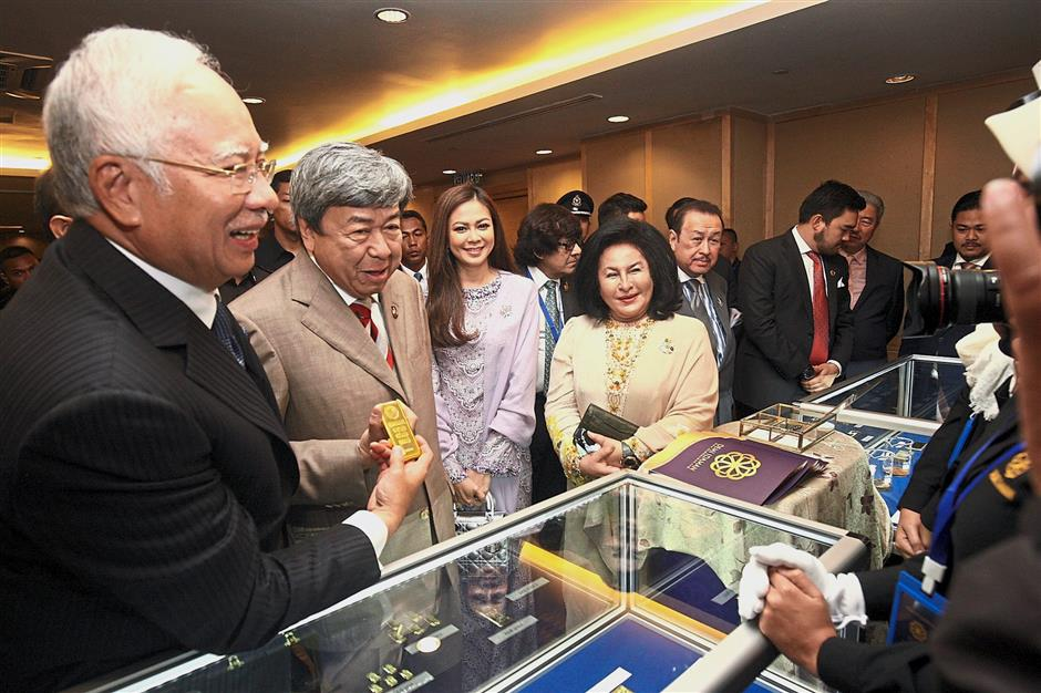 Honoured guests: Sultan Sharafuddin and Najib taking a closer look at the pure gold bars refined by Demi Idaman Sdn Bhd after the unveiling of the commemorative gold and silver coins (left) of Sultan Sharafuddin ?in Kuala Lumpur. Looking on are Tengku Permaisuri Norashikin and Rosmah.