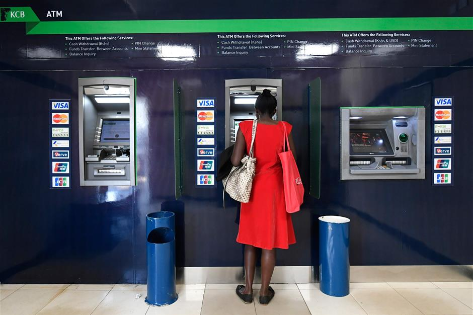A woman uses an ATM machine at the Kenya Commercial Bank (KCB) in Nairobi on January 24, 2018. / AFP PHOTO / SIMON MAINA