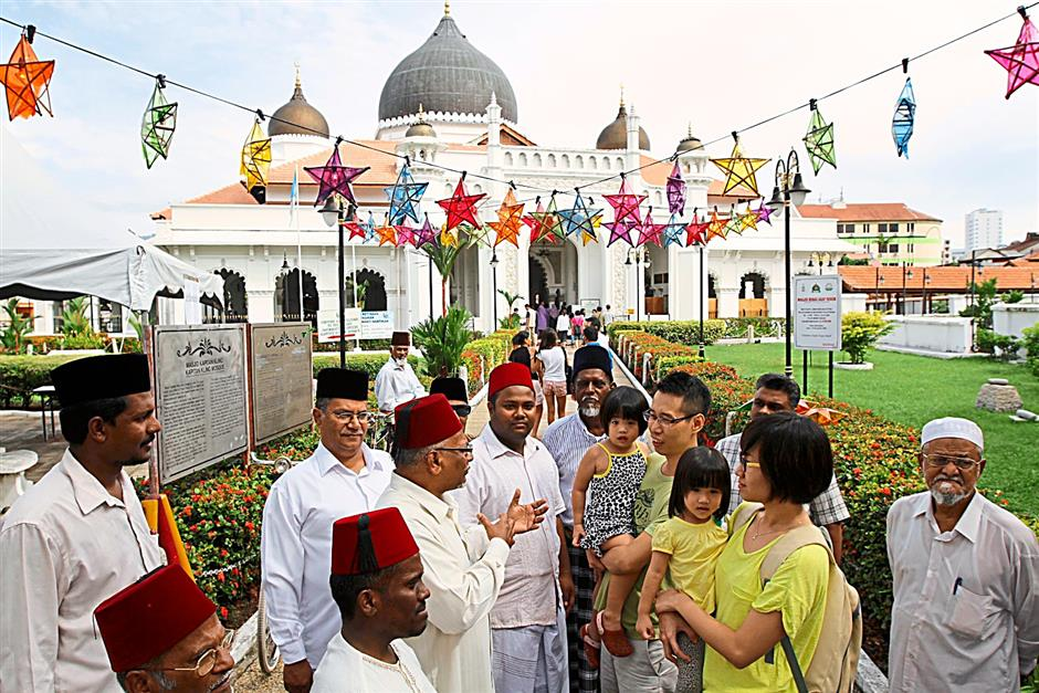 Landmark attraction: The Muslim Mosque committee members welcoming visitors to the Kapitan Keling Mosque during the George Town heritage site anniversary celebrations at Jalan Masjid Kapitan Keling.