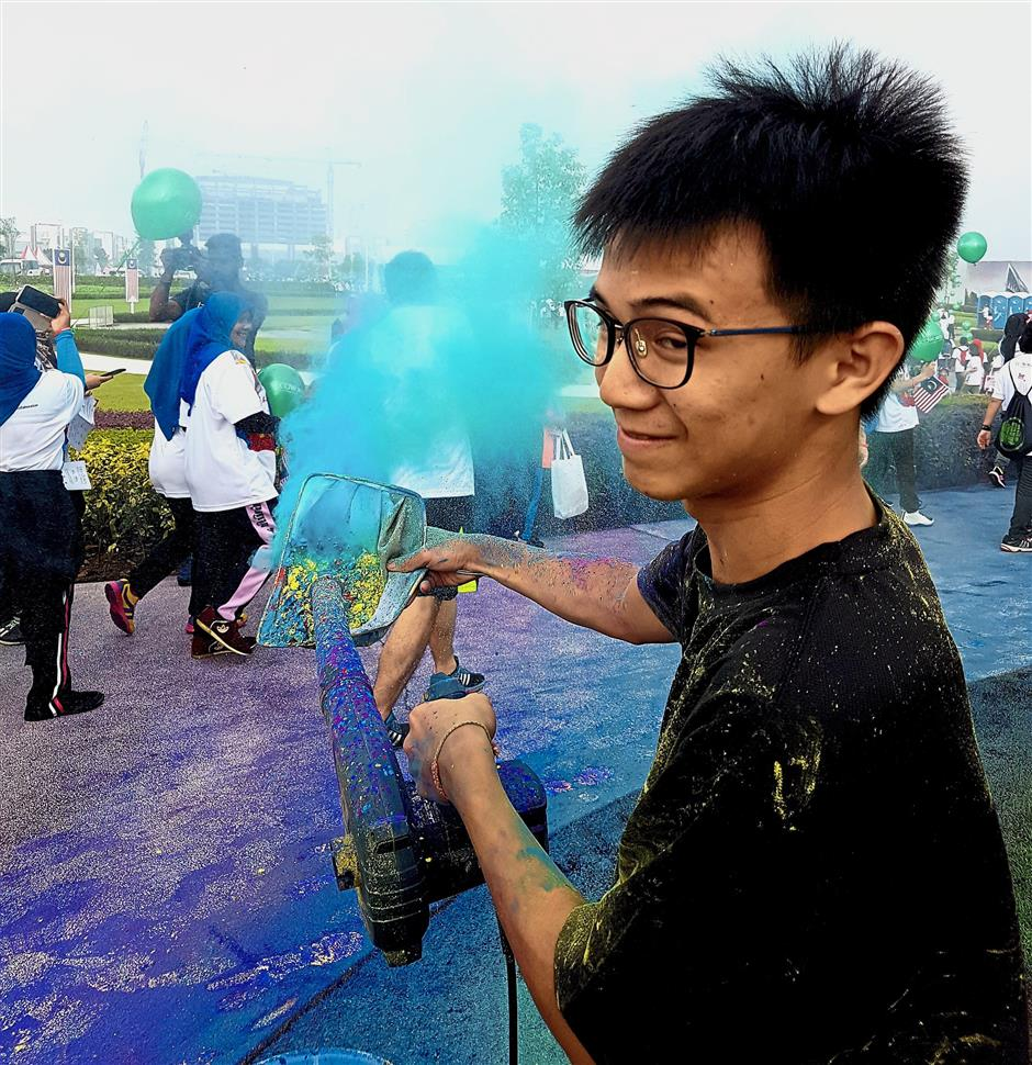 A volunteer of the organising team for AnakAnakMalaysia Walk grinning away as he creates a multicoloured dust storm for walkers.