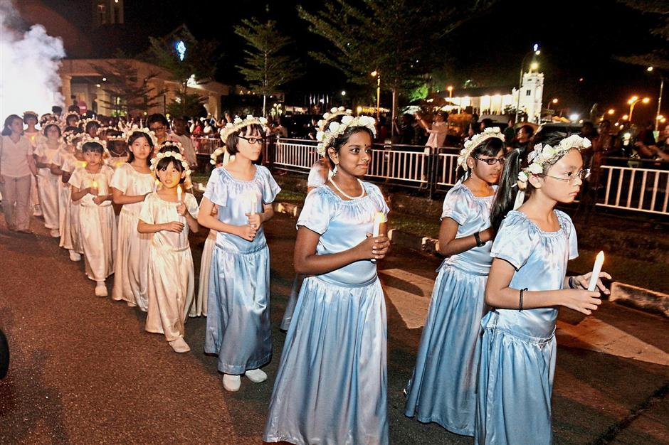 Girls wearing floral head wreaths taking part in the candlelight procession.