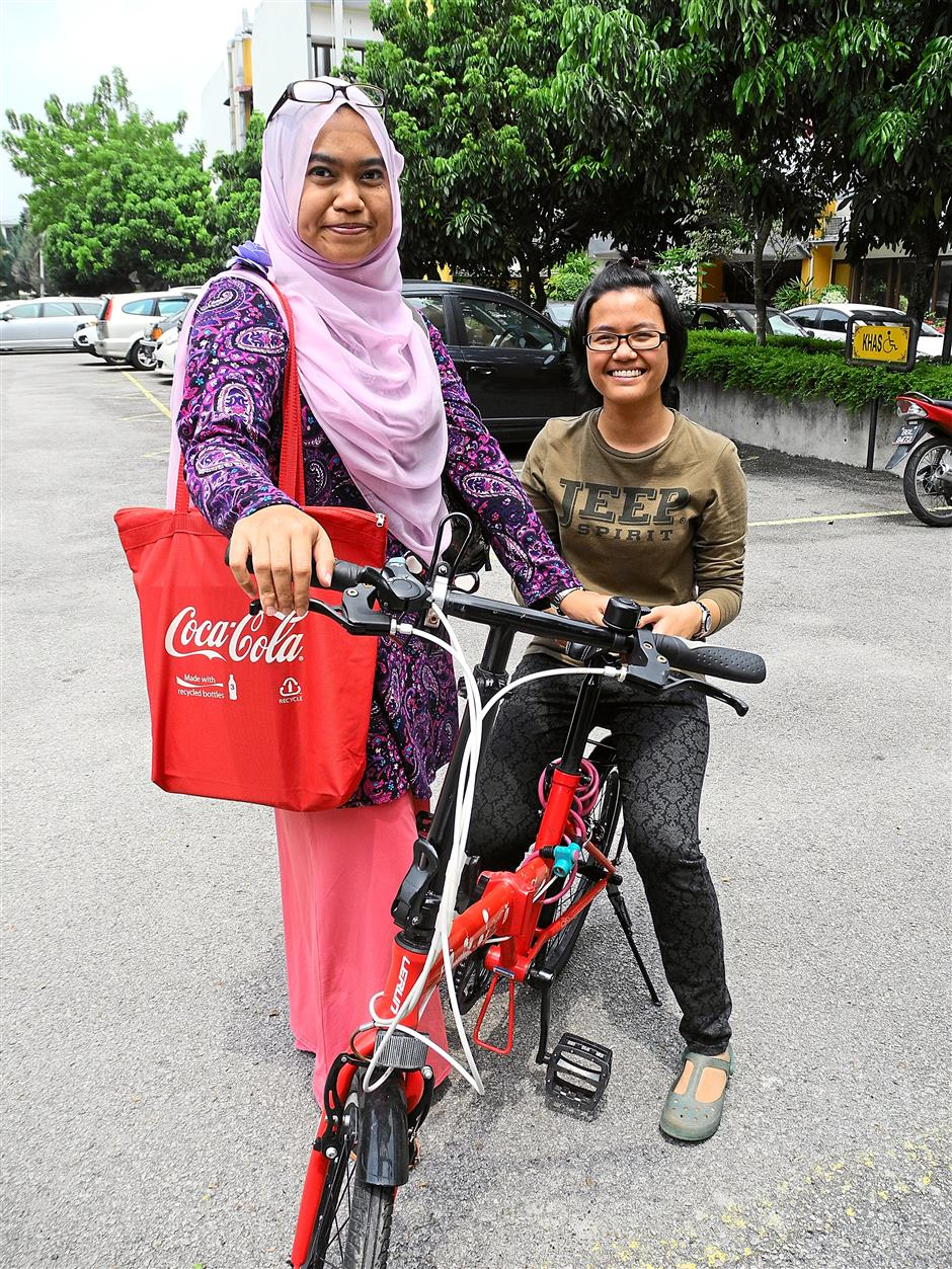 Students Nurfitri Liyana Shamshudin (right) and Nur Adilah Auyob have benefited from free use of bicycles daily while doing their bit for the environment.