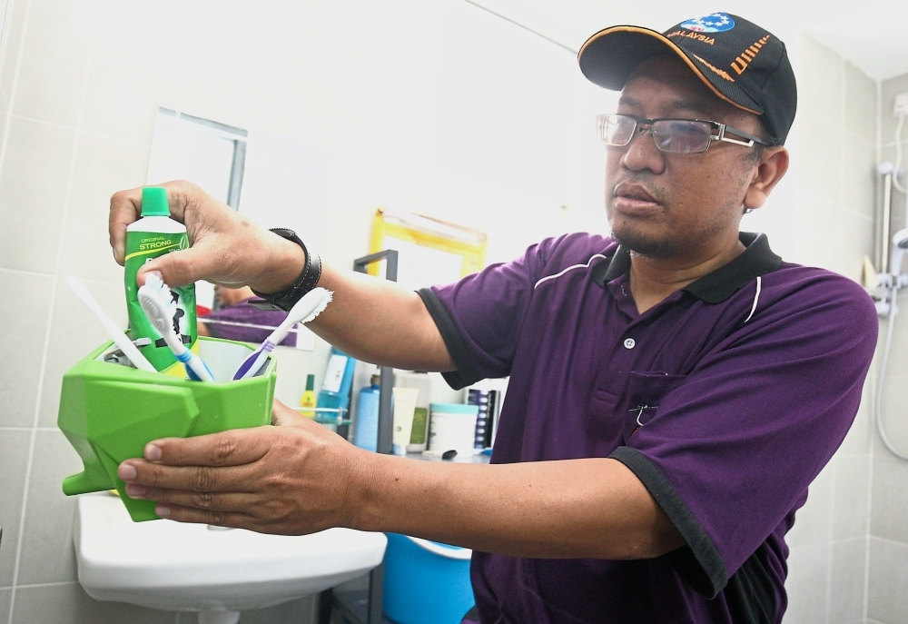Ahmad checking a toothbrush container for Aedes mosquito larvae at a unit in Damai Apartment.