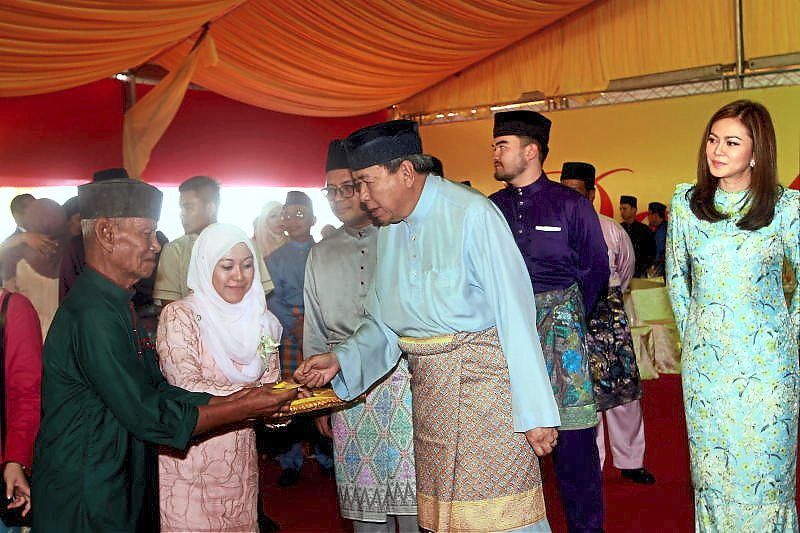 Sultan Sharafuddin giving out duit raya to the less privileged at the Selangor state Hari Raya open house in Shah Alam on June 24. Accompanying him are (from right) Tengku Permaisuri Norashikin, Raja Muda of Selangor Tengku Amir Shah and Selangor MB Amirudin Shari.