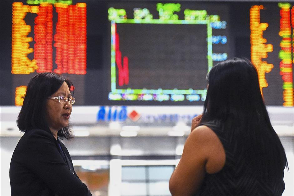 Investors stand in front of private stock trading boards at a private stock market gallery in Kuala Lumpur, Malaysia, Monday, Oct. 22, 2018. Asian markets were mixed on Monday although Chinese benchmarks rallied after officials put a positive spin on the country's slowing economy. (AP Photo/Yam G-Jun)