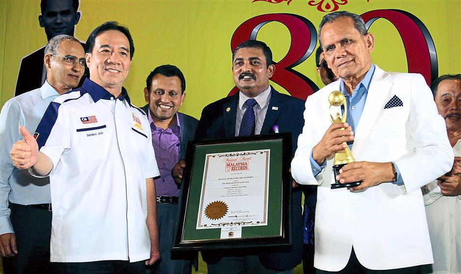 Well-deserved recognition: Santa Maria (right) holding the trophy while La Salle Sentul Old Boys Association president Magandran Muthiah helps to hold the Malaysia Book of Records certification, presented by Ooi (left) at the event.